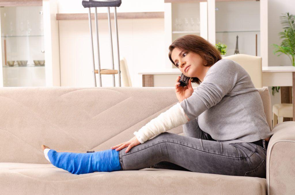 mladá žena s nohou v sádře telefonuje